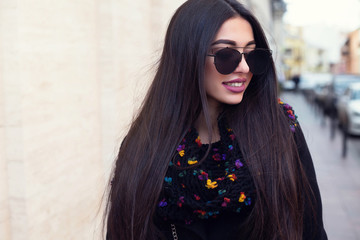 Outdoor fashion portrait of stylish young woman having fun. Fashionable woman in a hat, black jacket, sunglasses, boots, walking in the street.