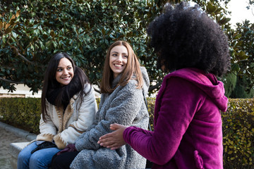 Multiethnic pretty women sitting on park bench and interacting in Madrid, Spain.
