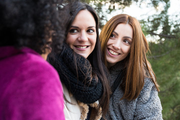 Pretty young women sitting in park together in Madrid, Spain.
