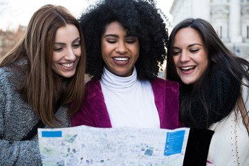 Three multiethnic female friends standing and reading map on street in Madrid, Spain.