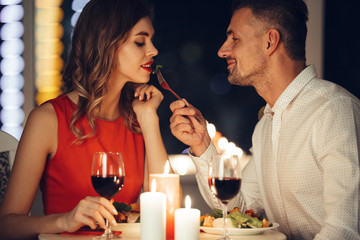 Smiling careful man feed his pretty girlfriend while have romantic dinner at home Fototapete
