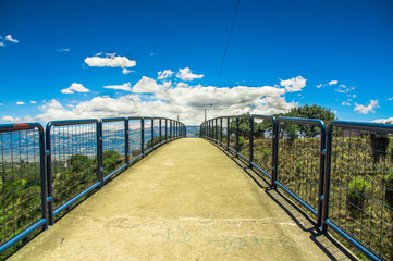 Outdoor view of pedestrian bridge over a road to visit the municipal dump in a beautiful day in the city of Quito, Ecuador