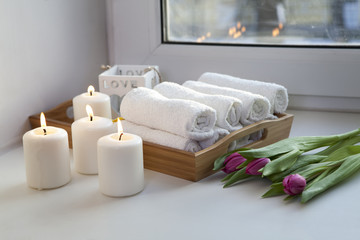 the Rolled hand towels on a tray next to the lighted candles and a bouquet of tulips in the spa salon