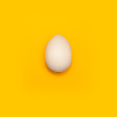 Happy Easter concept. Flat lay. Minimal concept. Top view. Wooden egg on yellow background.