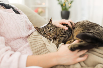 close up of owner with tabby cat in bed at home
