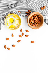 Use nut oil as cosmetics. Almond oil in jar near almond in bowl on white background top view copy space
