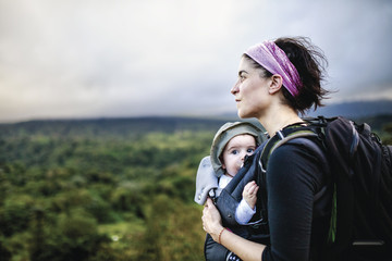 Mother and baby hiking over rural landscape