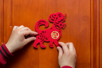 man sticking a Chinese New Year of the Dog 2018 to a door the Chinese means prosperous