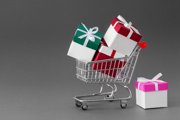 Mini shopping cart full of colorful gift boxes with ribbons. Gray background with copy space.