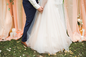 Bride and groom holding hands during their wedding ceremony outdoors. Horizontal coor photography.