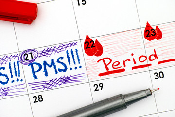 Reminder PMS and Period in calendar with red pen.