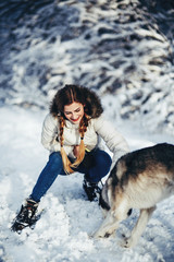 Pretty girl walks with a husky dog in a winter park full of snow
