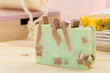 Handmade green soap on wooden background with toiletries in bathroom
