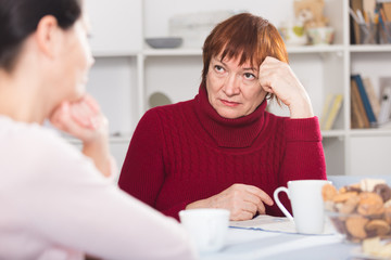 Upset woman with cup of tea  talking with daughter