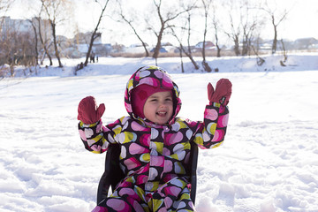 Happy little girl on sled on winter and snowy background. Child sledding