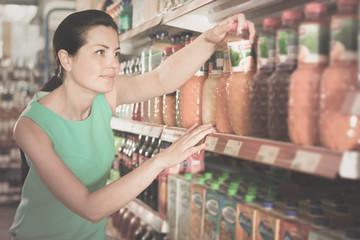 Woman in the supermarket choosing juice in bottle