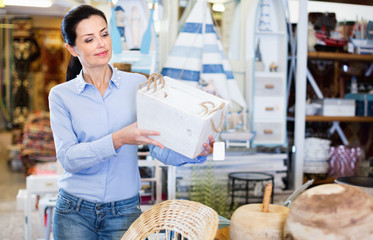 Woman standing with wooden box in decoration and furniture store