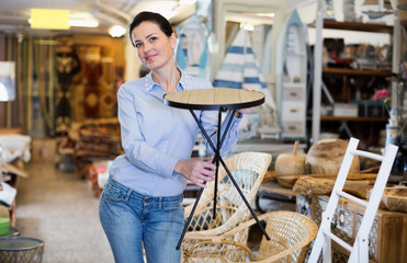 Smiling female holding wooden chair at store