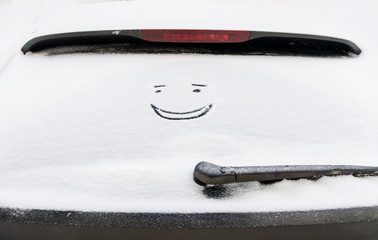 Snow smiling face on car