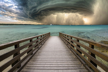huge tornado with a jetty in the foreground