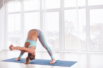 Beautiful young woman practices yoga asana Prasarita Padottanasana at the yoga class