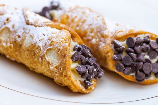 Italian cannoli on white plate with blackberries and chocolate chips