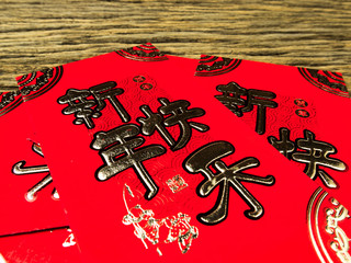 Red envelope on wooden background with February for gift Chinese New Year. Chinese text on envelope meaning Happy Chinese New Year
