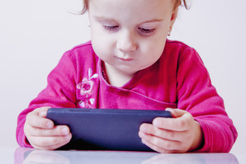 Little beautiful child girl using smartphone as symbol of work or study. Connect to the Internet with smartphone. (Development, education, technology concept)
