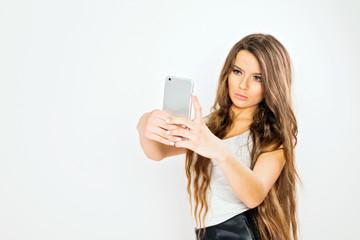 Gorgeous teenage girl with long blonde hair posing taking a selfie on smart phone