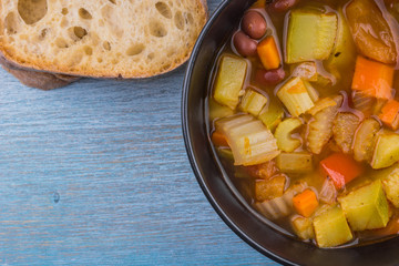 Vegetarian Italian soup and bread on a wooden background, copy space