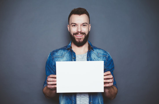 Everything is for you. Handsome young smiling man in a denim shirt shows a white sheet of paper in the camera on a gray background. Area for advertising.