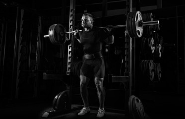 The weightlifter stands with a very heavy barbell on his shoulders.