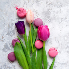 Pink and purple tulips and macarons on light textured background. Romantic congratulations concept with copy space.