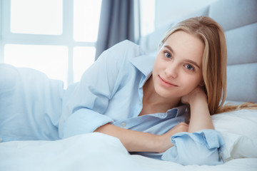 Young woman at home laying in bed woke up fresh