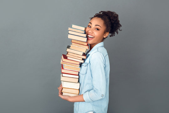 Young african woman isolated on grey wall studio casual daily lifestyle holding books profile