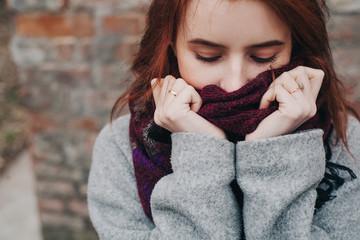 красивая молодая девушка в пальто закуталась в шерстяной шарф beautiful young girl in a coat wrapped in a wool scarf
