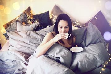 junge Frau im Bett mit Tasse Schlafzimmer Frühstück