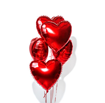 Valentine's Day. Air balloons. Bunch of red heart shaped foil balloons isolated on white background