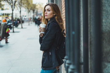 Woman with paper cup on street