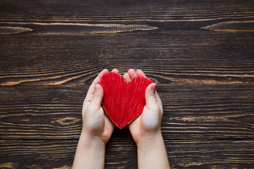 Children's hands giving red heart on a wooden background.