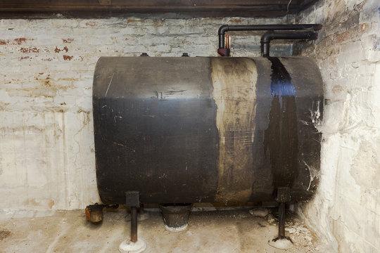 Old heating oil tank in dingy dank basement.