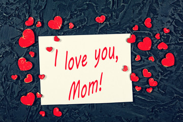 Red hearts and white blank sheet of paper on a black stone background. Valentine's Day, Mother's Day. I love you, Mom