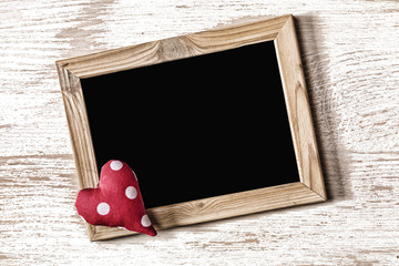 Frame of St. Valentine's Day and homemade heart on a white wood texture board