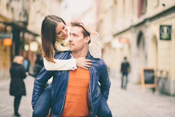Young man giving girlfriend a piggyback ride on the street