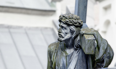 Ancient statue of Jesus Christ with cross. (holy, faith, religion, God, suffering concept)
