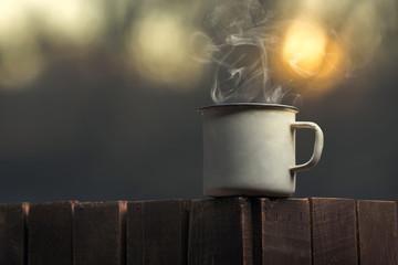 Hot drink in iron mug at sunset