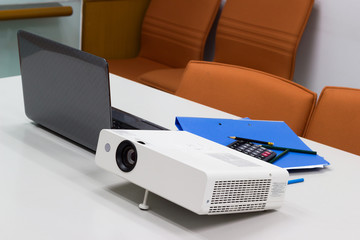 projector connected to Laptop with file folder on the table in a meeting room, Business Concept.