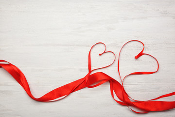 Hearts made of ribbons on wooden background
