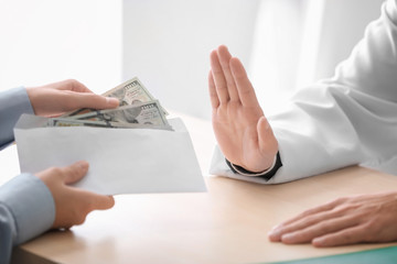 Doctor refusing to take money in envelope at table. Corruption concept