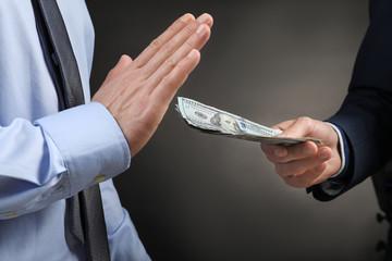 Businessman refusing to take money on dark background. Corruption concept